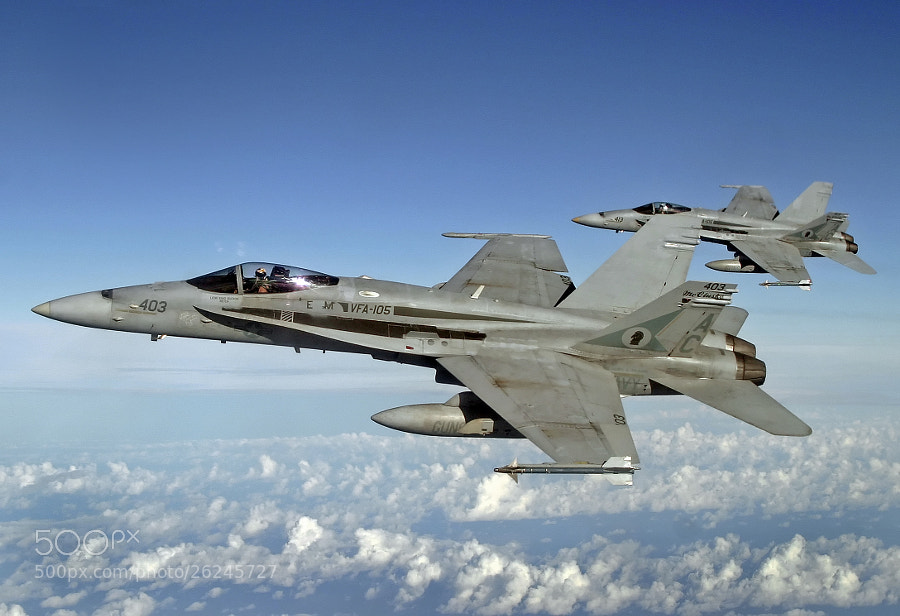 A pair of F/A-18C Legacy Hornets flying formation high over the Atlantic Ocean.