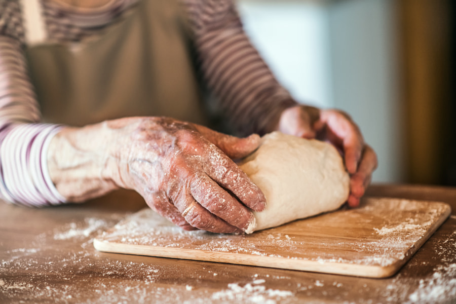 An unrecognizale senior woman kneading dough in the kitchen at home. by Jozef Polc on 500px.com