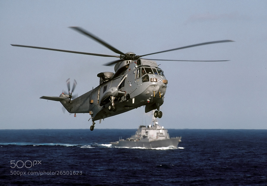 RN Seaking assigned to 820 Squadron, on approach to HMS Illustrious May 1996.  The USS Mitscher, DDG57, can be seen in the background on plane guard duty.  Scanned from an original slide.