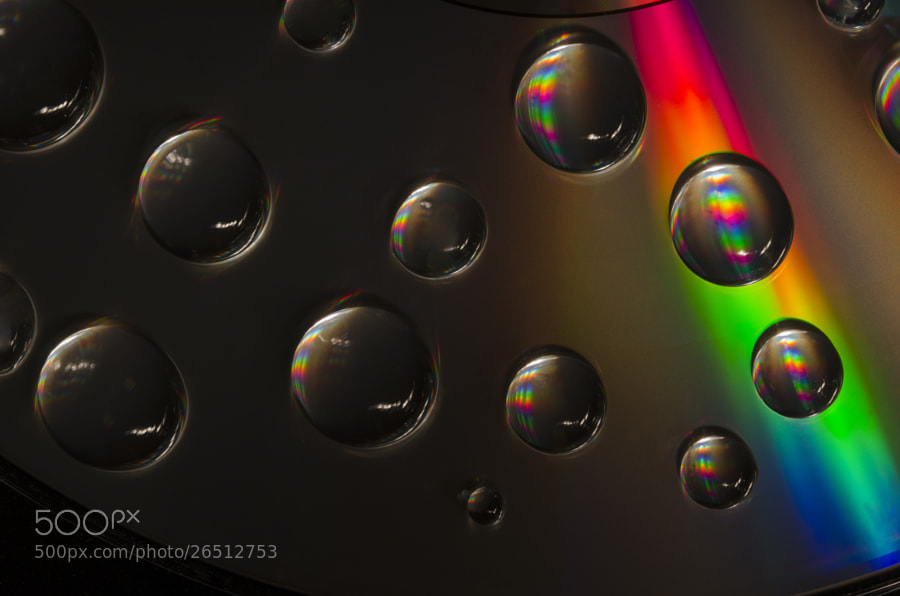 Liquid Rainbows. Water droplets on a CD