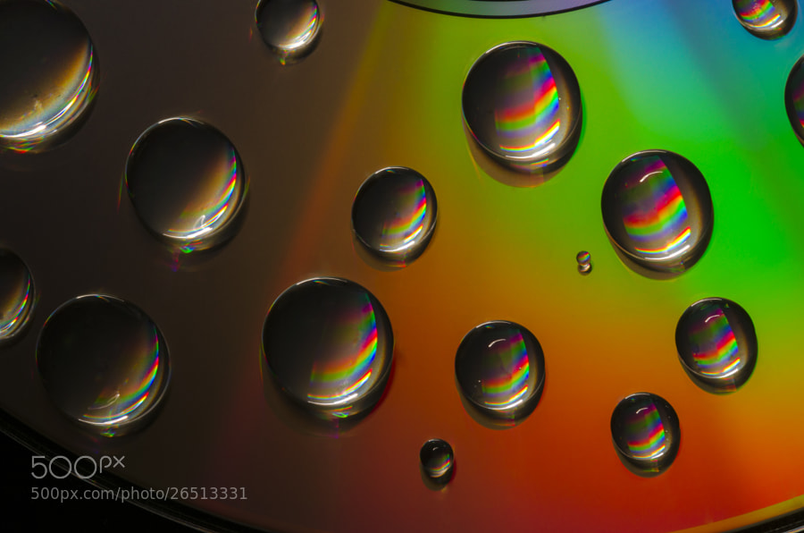 CD with water droplets, lit from low down by hand torch