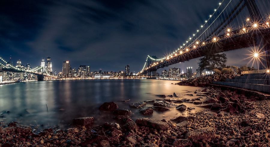 A night shot of the Manhattan and Brooklyn Bridges, shot from the DUMBO section of Brooklyn.