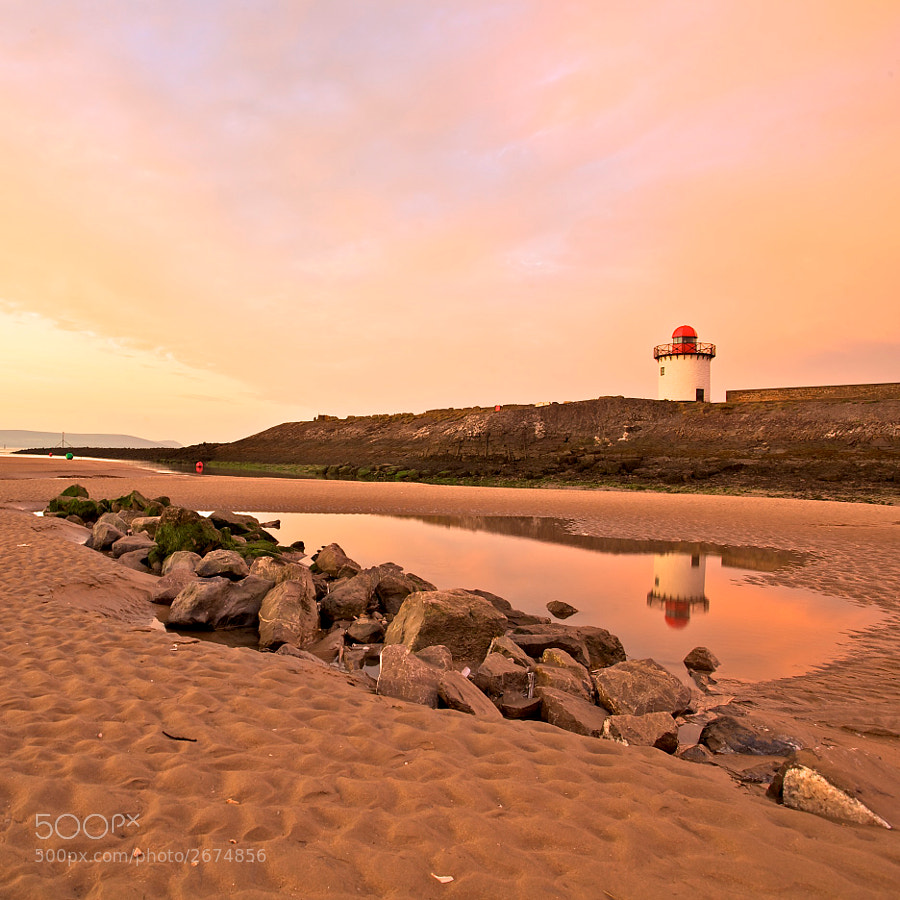 One from the archives as I've been poorly of late and unable to get out shooting (and test my new tripod).  Taken a few weekends ago, this is the harbour at sunrise. The tide was on its way in.  I liked the way the rocks lead your eye and the reflection of the light house in the pool.