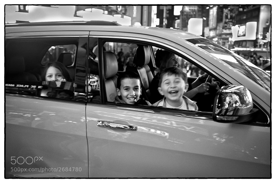 Three kids have a lot of fun as they are driven through Times Square