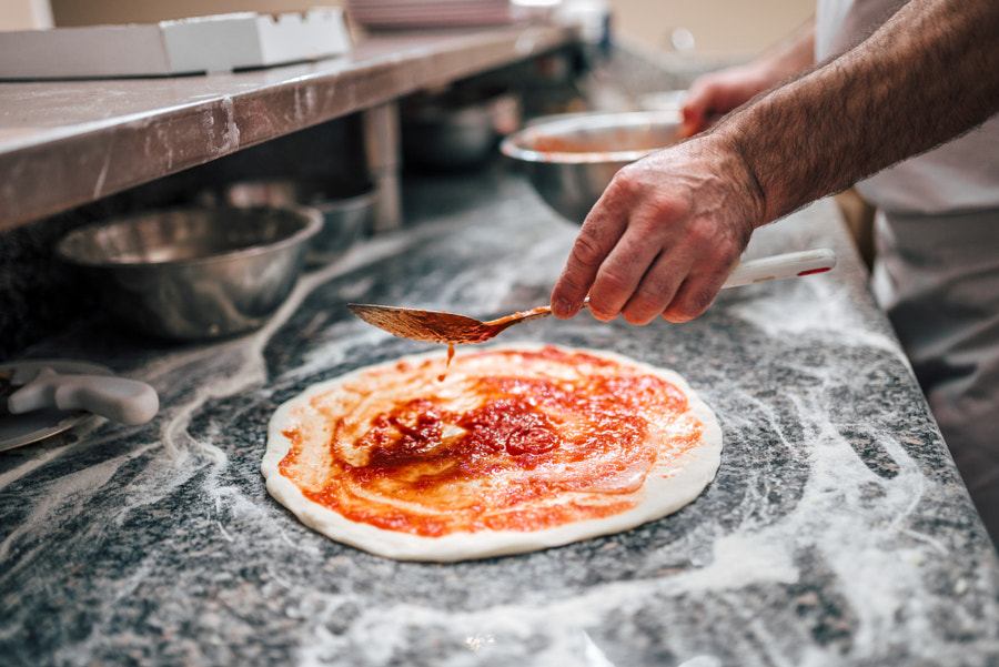 Preparing pizza. Chef's hand adding tomato sauce on pizza dough. by Branislav Nenin on 500px.com