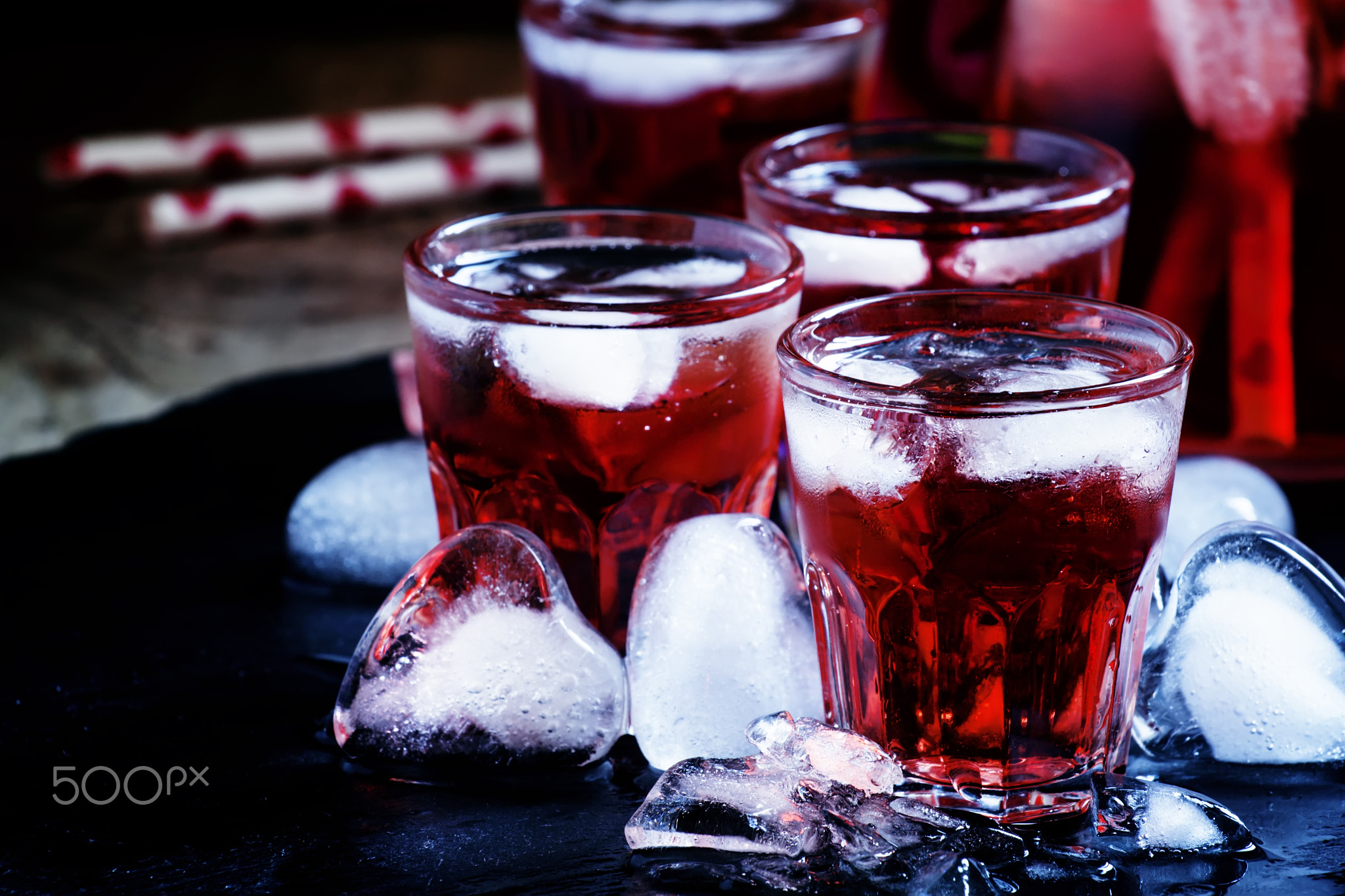 Red cocktail with ice in heart shape on a dark wet background, s