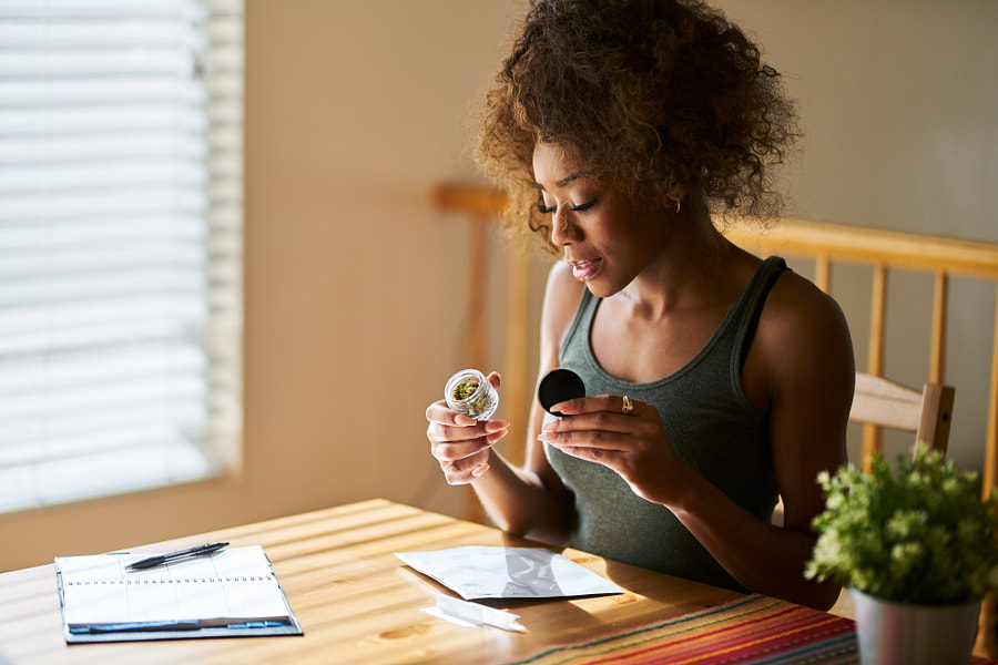 vrouw die thuis naar een container met marihuana kijkt die Joshua Resnick op 500px.com bij de legale apotheek heeft gekocht