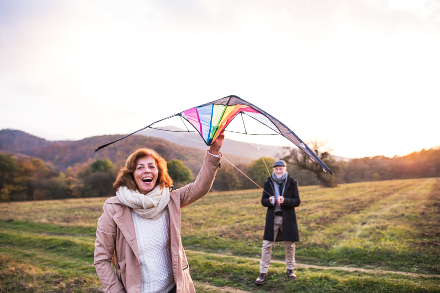 Carefree senior couple flying a kite in an autumn nature at sunset. by Jozef Polc on 500px.com