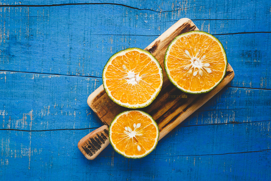 Orange slices on the blue wood background by Thai Thu on 500px.com