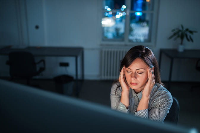 Tired and exhausted young woman sitting in front of computer scr
