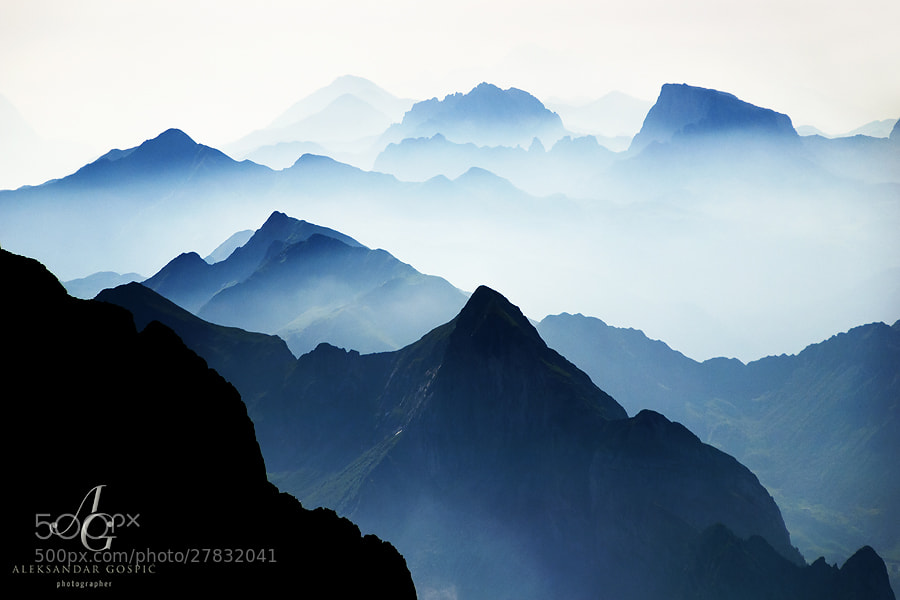 Peaks and ridges of Carnic Alps disappear into the early summer haze.  Photo taken in the early morning from the highest summit of the range, Hohe Warte/Coglians (2782m).  Austria/Italy