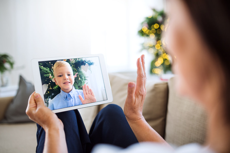 A grandmother with tablet making videocall with small grandson at Christmas time. by Jozef Polc on 500px.com
