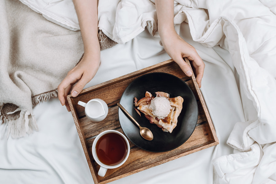 Cozy flatlay of bed, woman's hands holding wooden tray with vega by Nataly Lavrenkova on 500px.com