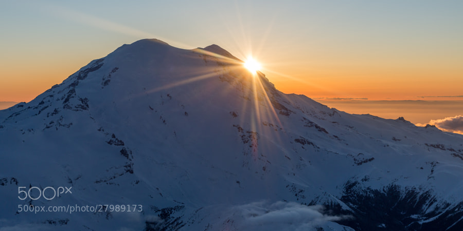 The sun peaks around Liberty Cap on Rainier's northern summit.