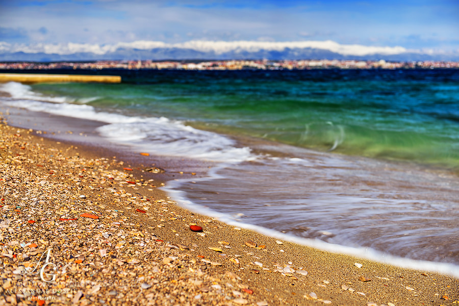 And the sea also wants the most beautiful stone on the beach. In the distance are Zadar city and Velebit mountain.