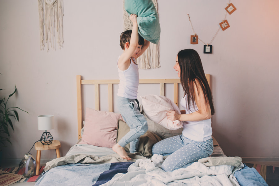happy mother and child son playing pillow fight in bed in early morning. Family casual lifestyle... by Maria Kovalevskaya on 500px.com