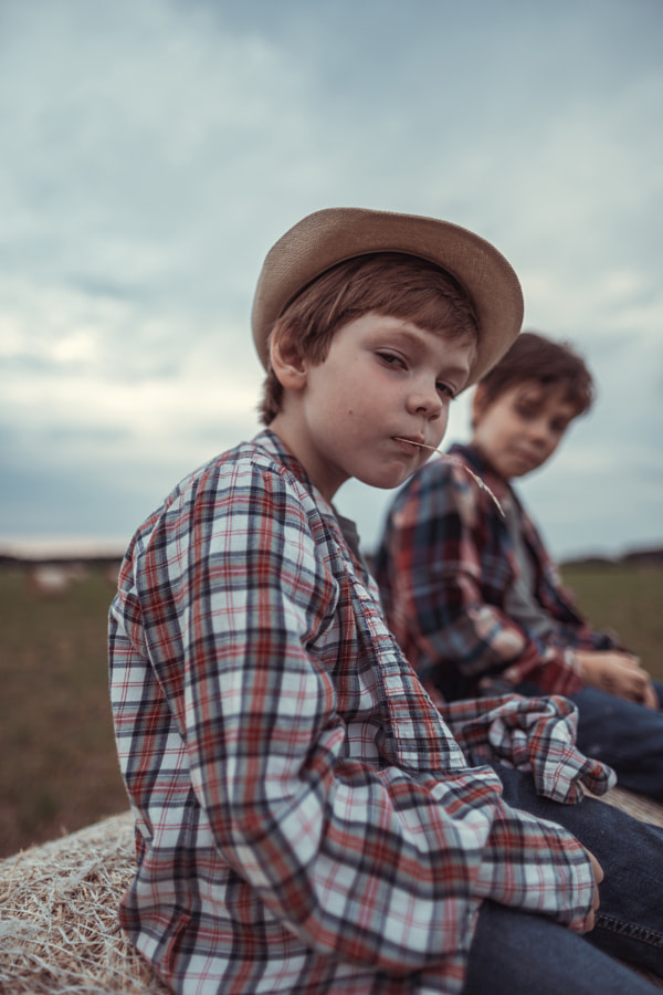 Two brother sitting on a haystack in the field by Irina Polonina on 500px.com