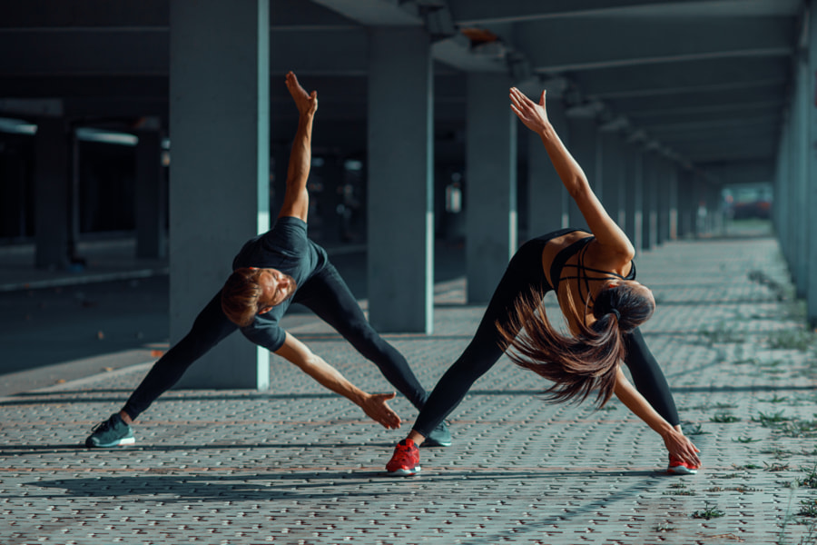 Young couple warming up in urban environment before jogging by Milenko ?ilas on 500px.com