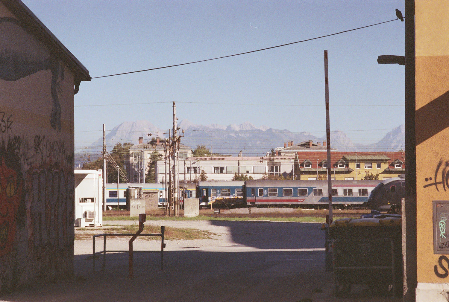 Passenger train cars in red, blue, and silver livery wait in their tracks. Behind, low buildings, and even further, pale mountains. The sky above is a daytime blue. Framing the scene on the left is the shadowed, graffitied wall of a building. A dumpster sits next to the sunlit yellow wall on the right. A line connects the two buildings, upon which a bird sits, shaded