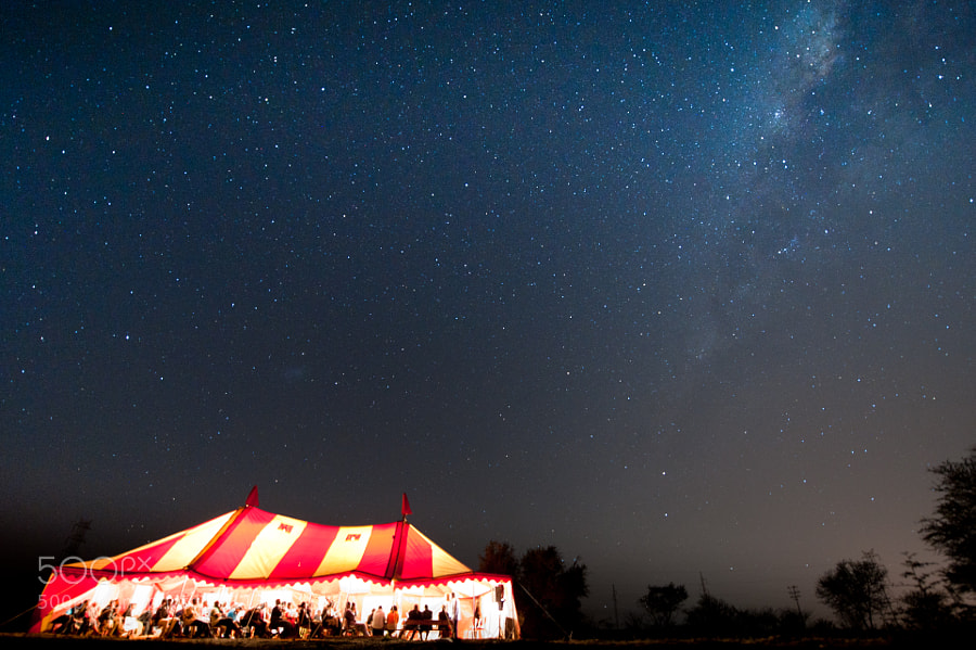People meeting under a large tent under the stars in Zimbabwe.