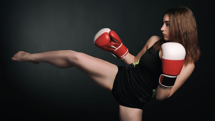 Beautiful young woman in a red boxing gloves over black background by Кирилл Бусаргин on 500px.com