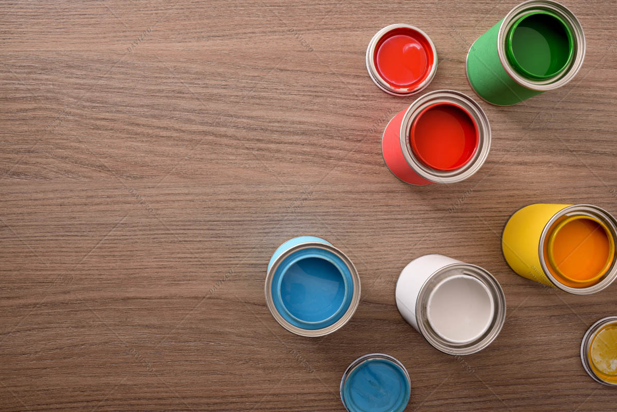 Five open paint cans and their covers on table top