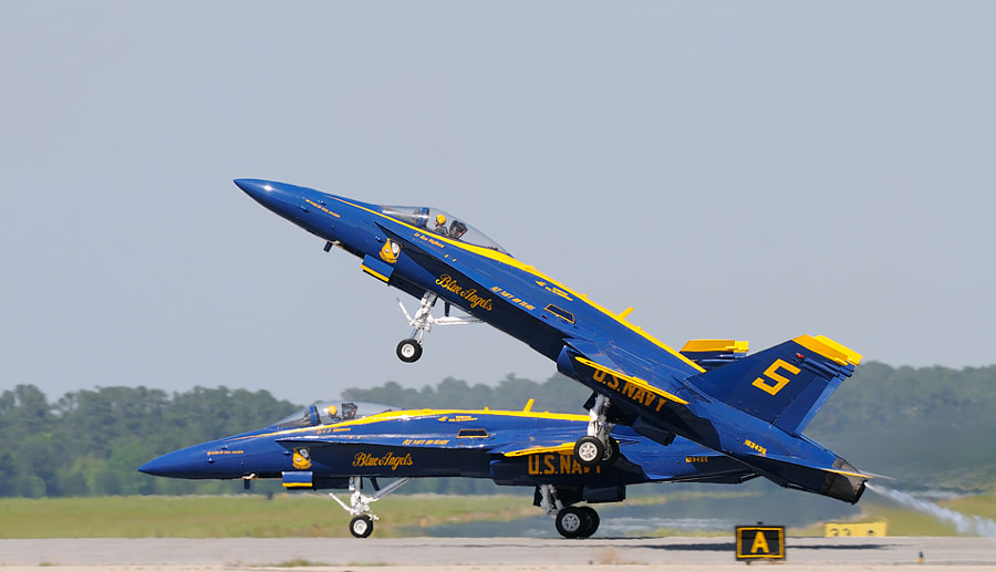 While Blue Angel number 5, Lieutenant Commander Ben Walborn, in the foreground already is airborne, Blue Angel number 6, Lieutenant C.J. Simonsen, in the background, still is making speed with all wheels on the runway. Shot taken during an Airshow  at  MCAS Beaufort, South Carolina, May this year.  Best regards and have a nice Sunday,  Harry