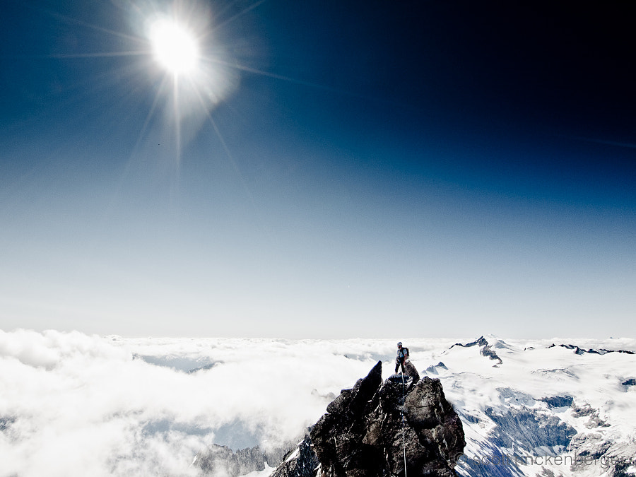 Matt Henry above the clouds on top of spectacular Forbidden Peak in the north Cascades of Washington State.