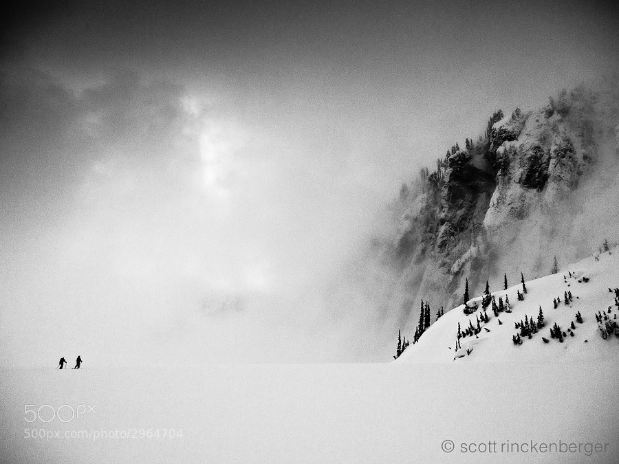 A wall of fog encroaches on two skiers crossing frozen Snow Lake in the Washington Cascades.