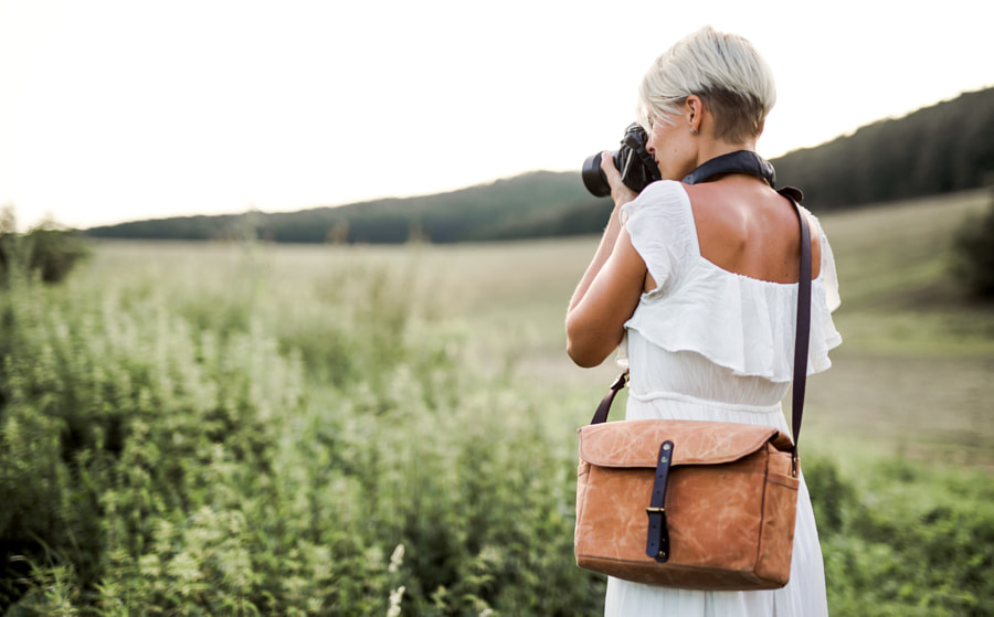 A rear view of woman with camera in nature, taking photographs. Copy space. by Jozef Polc on 500px.com