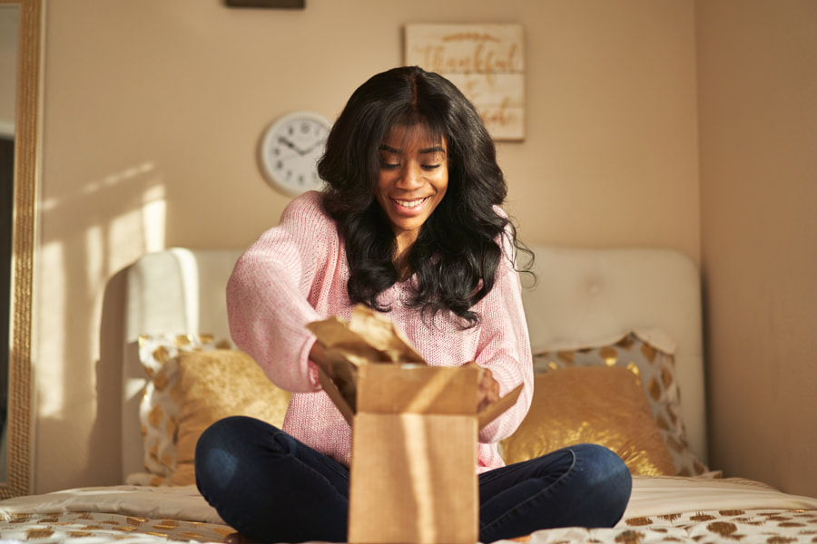 african american woman opening box on bed by Joshua Resnick on 500px.com