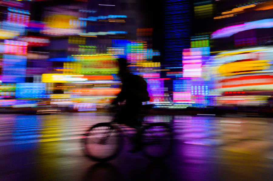 motion blurred of rider ride bicycle with neon light background by WATCHARAPONG THAWORNWICHIAN on 500px.com