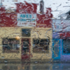 Abe's and Bubble Tea, in the rain, on Main. Through the car windshield, early on a dark and wet Vancouver morning.  This is a composite image, taken with the camera resting on the steering wheel. It combines one shot focusing on the rain on the windshield, and the other shot focusing on the colourful storefronts, after a wiper pass.