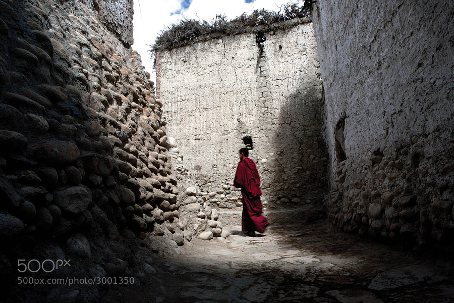 A monk walks through the alleyways of Lo Manthang.