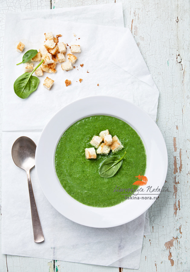 Spinach soup with croutons in white bowl