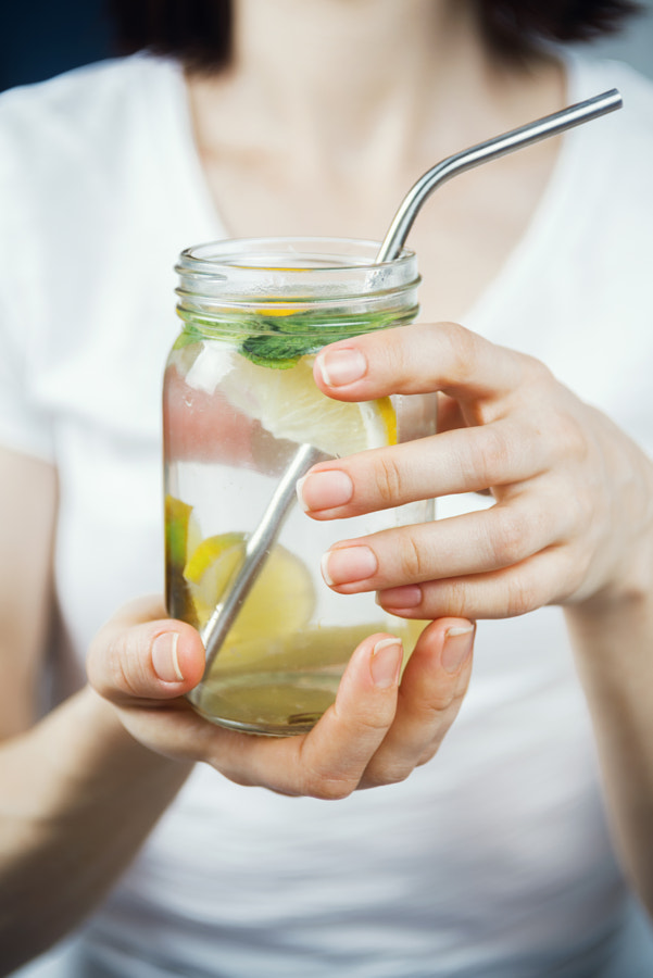 Closeup of woman's hands holding mason jar with sassy lemon and mint water, selective focus by Nataly Lavrenkova on 500px.com
