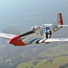 """P-51D Mustang """"Red Nose"""" prepares to slip behind the C-45 photo ship."""