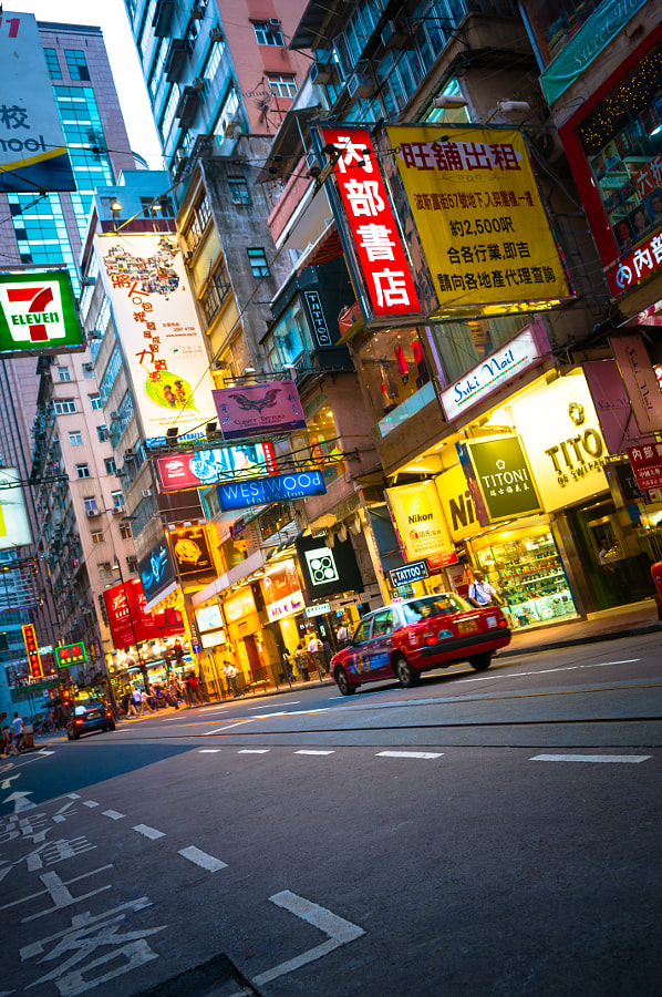 Typical street view in Hong Kong with illuminated signs, red taxis, and camera shops