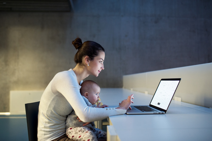 Young student with a baby sitting on desk in room in a library or office, using laptop. by Jozef Polc on 500px.com