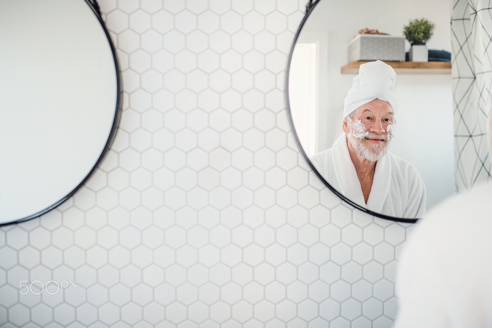 A senior man doing morning routine in bathroom indoors at home. Copy space.