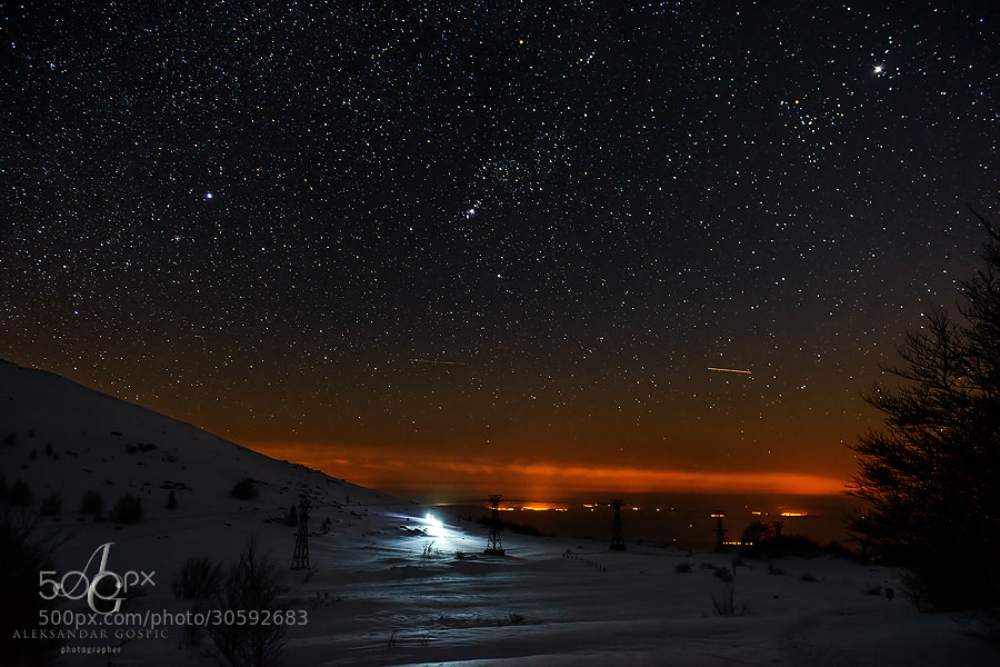 Through the Velebit night group of mountaineers advances towards the Veliki Alan pass. In the middle is Orion constellation with Orion nebula being brightest. Brightest star on the left is Sirius, while in the upper right is Jupiter.