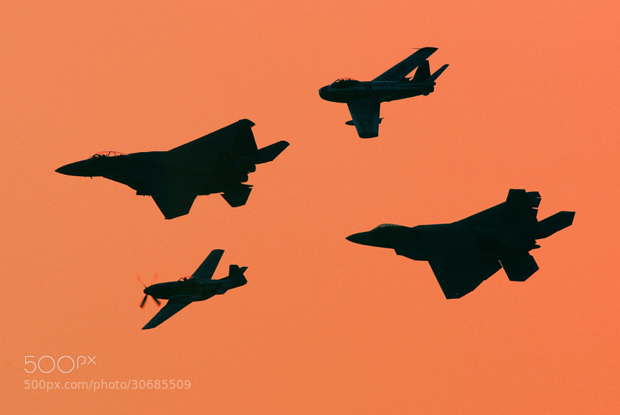 """No Military Air Shows in the USA this year has driven me to my archives for therapy.  This image depicts a F-15E Strike Eagle, P-51D Mustang, F-86 Sabre and F-22 Raptor.  When flying in formation at an air show, they became a """"Legacy Flight.  This one is from the 2007 NAS Oceana Air Show."""