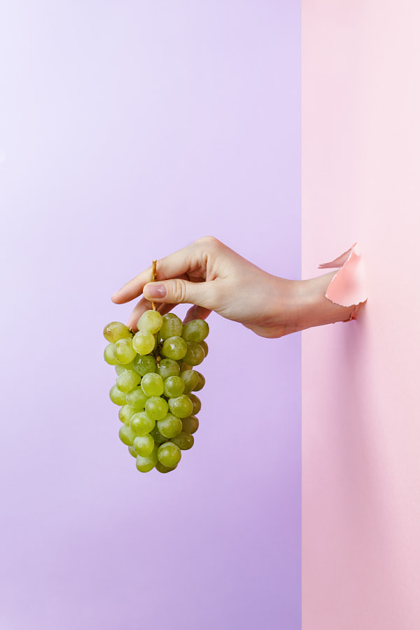 Woman's hand holding ripe green grape through pastel torn paper by Nataly Lavrenkova on 500px.com