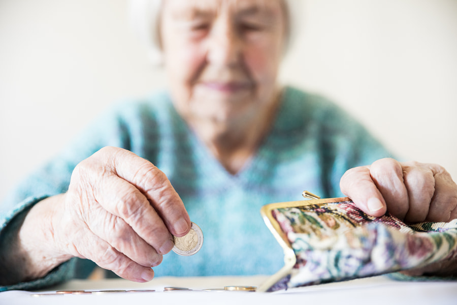 Concerned elderly woman sitting at the table counting money in her wallet. by Matej Kastelic on 500px.com
