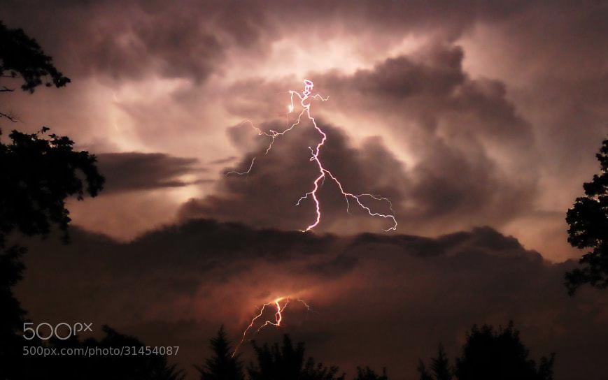 A Bolt of lightning through a lower deck of clouds.