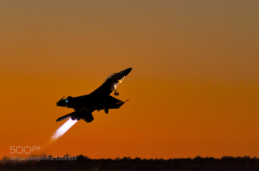 An F/A-18F Super Hornet takes off after sunset with afterburners blazing to begin the 2011 NAS Pensacola night show