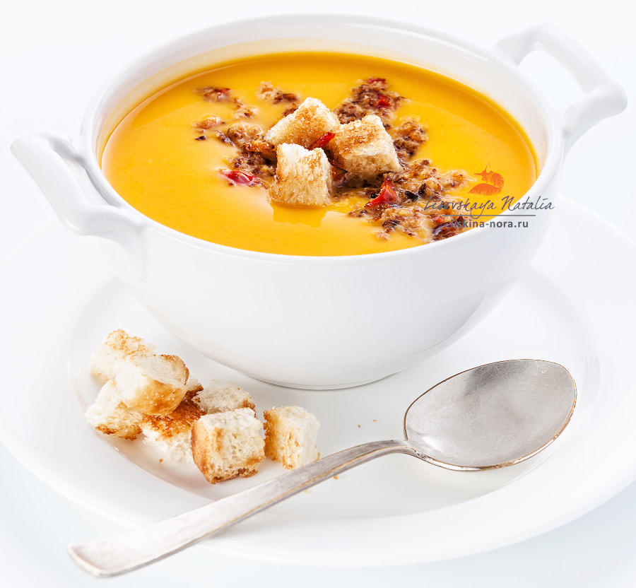 Pumpkin soup with croutons on white background