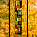 Fall colours on a hawthorn tree through stained glass hanging in a window.