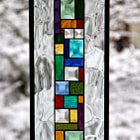 Snow on a hawthorn tree, through stained glass hanging in a window.