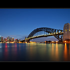 This morning, I found myself immersed in a bizarre combination of three unusual circumstances:  1.  I went out for a dawn shoot. 2.  I wanted a plain sky. 3.  I photographed the Sydney Harbour Bridge.  These days, each of these factors on its own is quite rare.  Firstly, I seldom get time or motivation to head out at dawn. With more or less three jobs, when I get time on the weekend, I look forward to not having to be anywhere, and rising at 3am and travelling somewhere for a dawn shoot is usually far from my mind.  Secondly, I cannot stand plain skies, and generally do not even shoot if there isn't good cloud cover. I keep an eye on weather and sky condition forecasts so I know whether or not it's worth heading out. Apart from plain skies being very boring, the light is harsh and difficult to shoot, particularly when facing east.  Thirdly, I rarely shoot the Sydney Harbour Bridge. It's a subject that has been shot to death by seemingly just about every photographer who lives in Sydney, or who has visited Sydney. It generally bores me in the photographic sense, and apart from one aerial flight during which I captured it from the sky, this is the first time I've photographed the bridge in a good five years.  Because I haven't been out for shoots much lately, and with my recent holiday period starting, I felt the itch, and wanted to take advantage of some free time before heading to London late this week.  My original plan was to head out on Monday night and shoot a twilight cityscape, but the weather forecast was for cloud and possible rain, and sure enough, the cloud rolled in and would have ironically spoiled the image I had in mind.  So, I decided to head out for a shoot on the following morning.  Inspired by an image captured by a contact of mine, I headed to Kirribilli, on the north shore of Sydney Harbour.  I had never visited this location, let alone shot from it.  I arrived nice and early, and captured a few images from my location during the morning blue hou